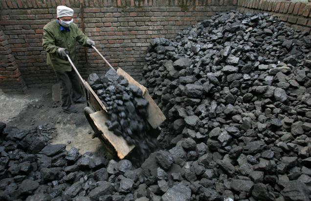 Man working with a mountain of coal